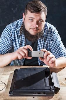 O engenheiro faz fotos do laptop na câmera do telefone. tecnologia de reparo de dispositivos eletrônicos