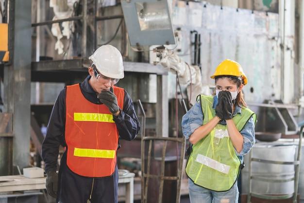 O engenheiro fêmea asiático que desgasta a máscara higiênica protege olhar o coordenador masculino que espirra em suas mãos na fábrica