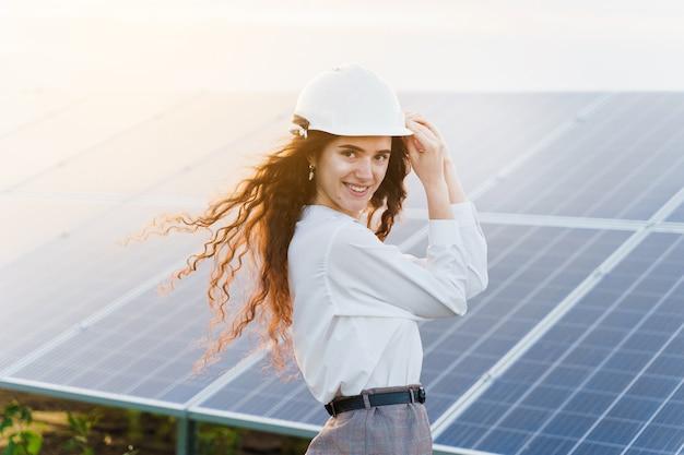 O engenheiro fica perto das fileiras de painéis solares ao pôr do sol