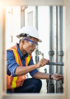 O engenheiro masculino tailandês está verificando a ordem dos contêineres da empresa.