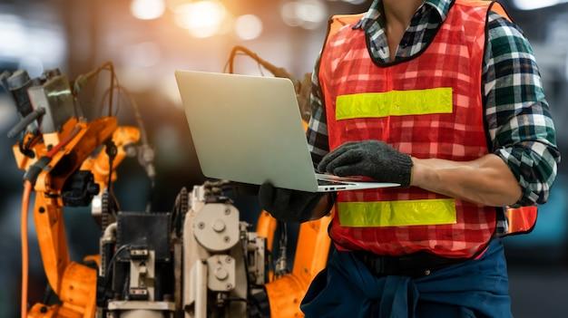 O engenheiro usa software robótico avançado para controlar o braço do robô da indústria na fábrica