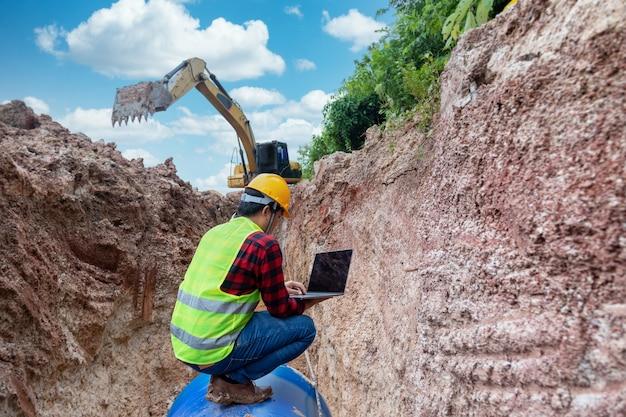 O engenheiro usa uniforme de segurança e usa laptop examinando o tubo de drenagem da escavação