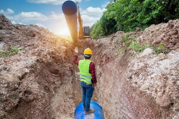 O engenheiro usa uniforme de segurança examinando o tubo de drenagem da escavação