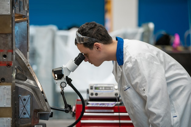 O engenheiro verifica a configuração correta do molde de metal para ver se há peças fundidas na fábrica usando um microscópio