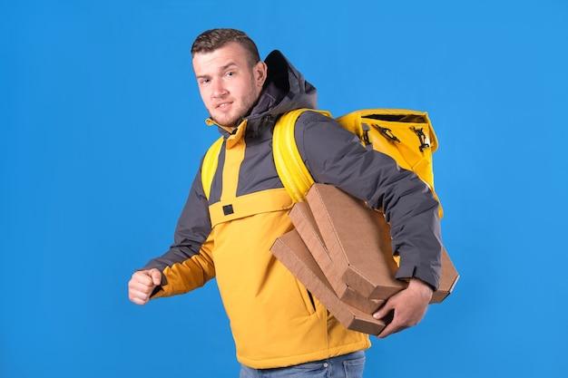 O entregador de comida jovem loiro caucasiano com barba por fazer em uniforme amarelo de marca está andando e segurando caixas de pizza do restaurante,