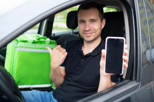 O entregador de comida tem uma mochila de geladeira verde. ele senta em um carro. ele mostra a tela de um smartphone com um aplicativo de entrega de comida.