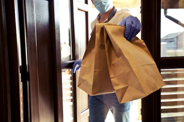 O entregador de comida, usando luvas e máscara facial, está entregando o pedido ao cliente em casa