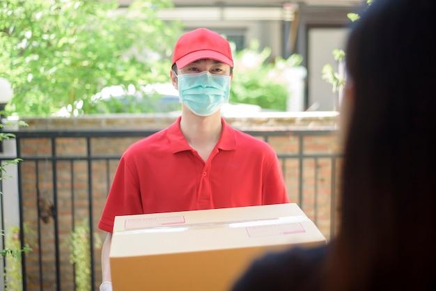 O entregador de máscara e luvas protetoras entrega comida de caixa durante o surto de vírus. entrega em domicílio segura.