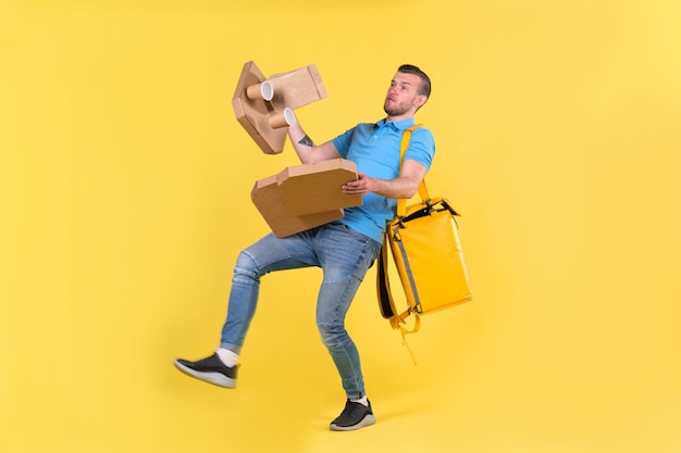 O entregador de uniforme azul escorregou e perdeu o equilíbrio e jogou caixas de comida do restaurante na direção