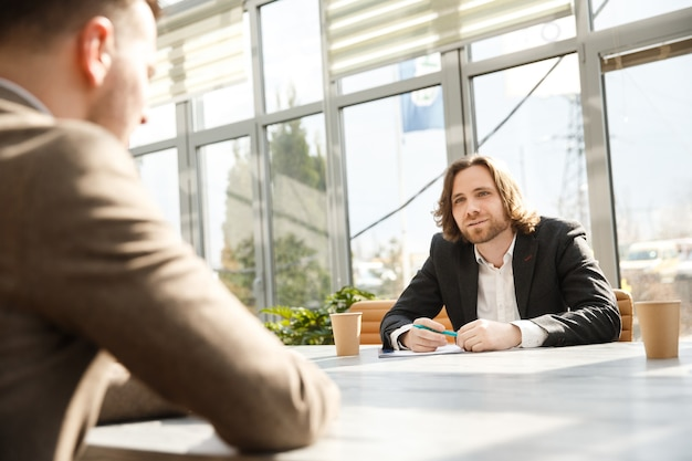 O entrevistador está questionando um candidato em uma entrevista de emprego.