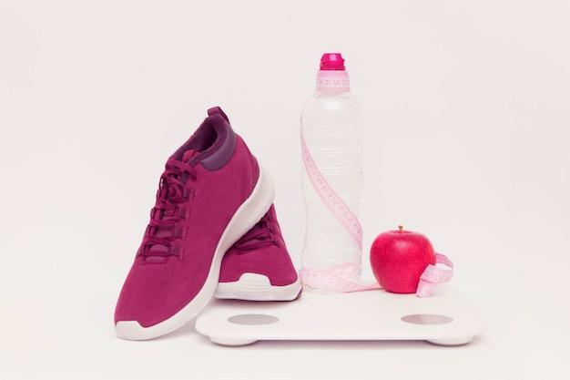 O equipamento de esportes, maçã e escala uma água de garrafa em um fundo tonificado.