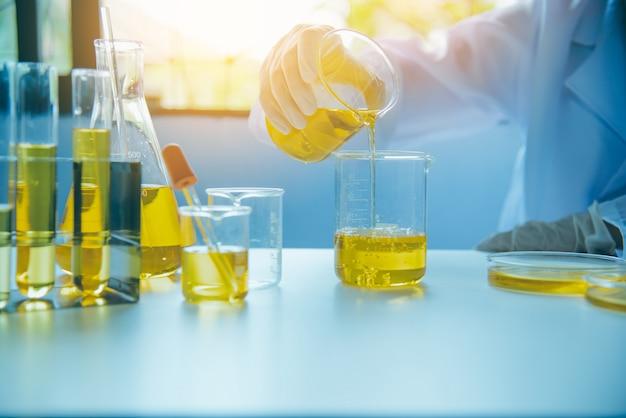 O equipamento e a ciência experimentam o cientista de derramamento do óleo com o amarelo do tubo de ensaio que faz a pesquisa no laboratório.