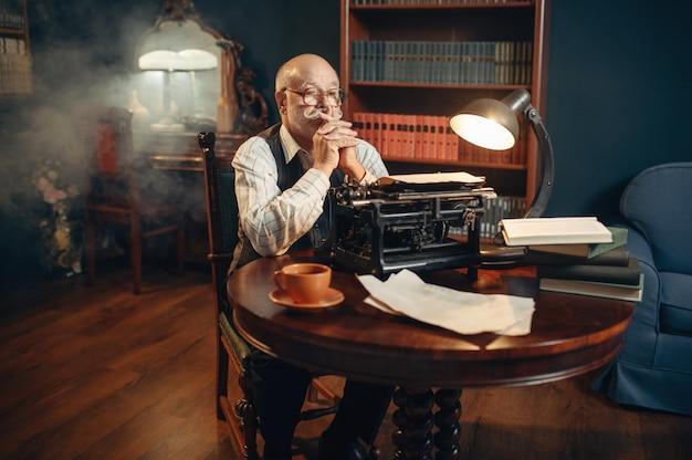 O escritor idoso pensa na máquina de escrever vintage no escritório em casa. velho de óculos escreve romance de literatura em uma sala com fumaça, inspiração