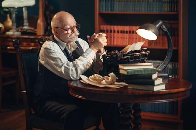 O escritor idoso pensa na máquina de escrever vintage no escritório em casa. velho de óculos escrevendo romance de literatura em uma sala com fumaça