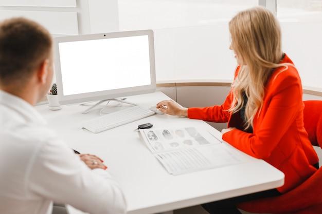 O escritório onde o cliente sentando e o negociante para a venda de carro durante o acordo