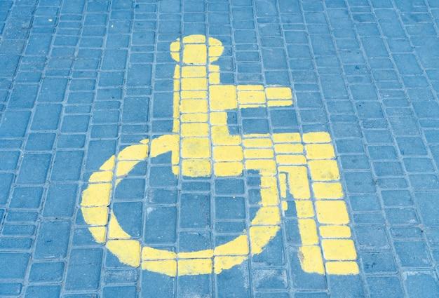 O espaço de estacionamento de carros para pessoas com deficiência o sinal desenhado na telha da estrada.