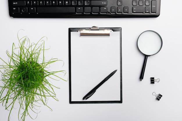 O espaço de trabalho da mesa de escritório domiciliário com teclado, a pena, a lupa, os grampos e a planta pretos do escritório.