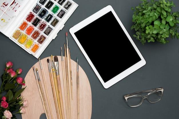 O espaço de trabalho do artista com laptop, tintas, pincéis, flores na superfície preta