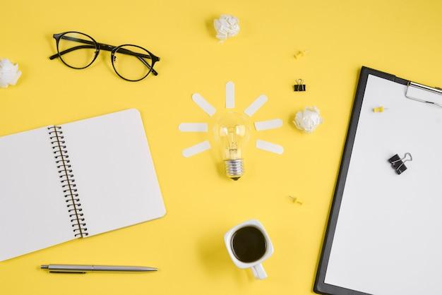 O espaço de trabalho do escritório com placa de grampo em branco, materiais de escritório no fundo amarelo.
