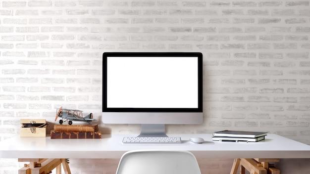 O espaço de trabalho do sótão com computador de secretária da tela vazia fornece na tabela branca.