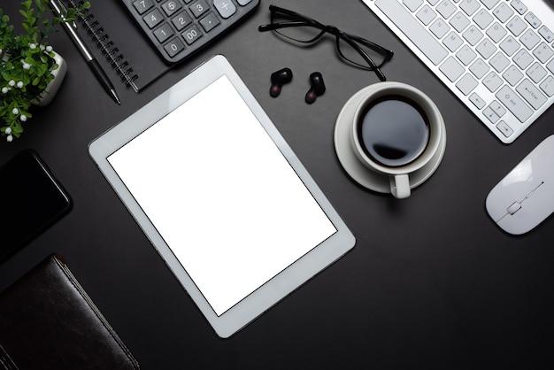O espaço de trabalho tem uma tela branca em branco de tablet com dispositivos de trabalho