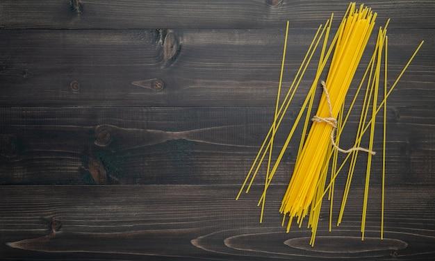 O espaguete fino no fundo de madeira preto.