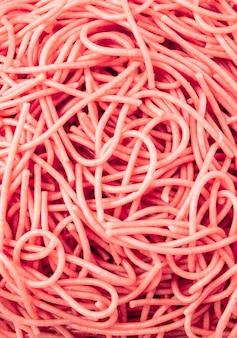 O espaguete integral sem glúten cor-de-rosa textured o fundo visto de cima de. conceito de comida saudável sem glúten