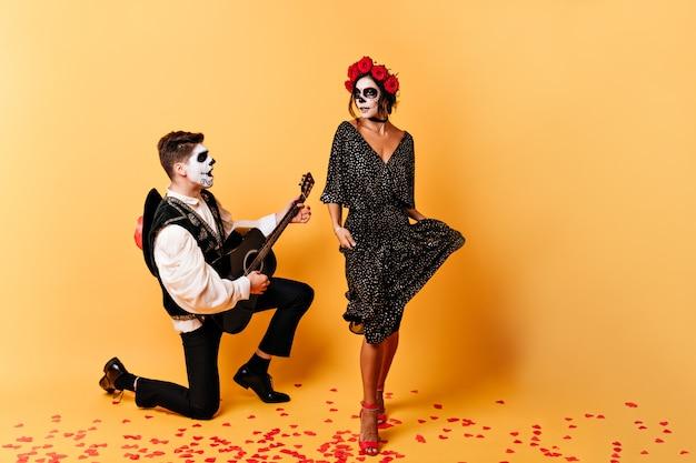 O espanhol em traje nacional canta sua música favorita. menina emocional com máscara de esqueleto no rosto dançando na parede laranja