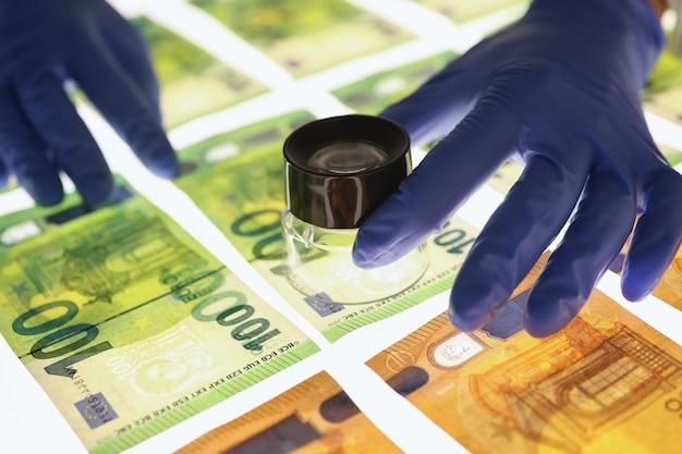 O especialista com luvas verifica a autenticidade das notas de euro, avalia o papel que as notas de banco são