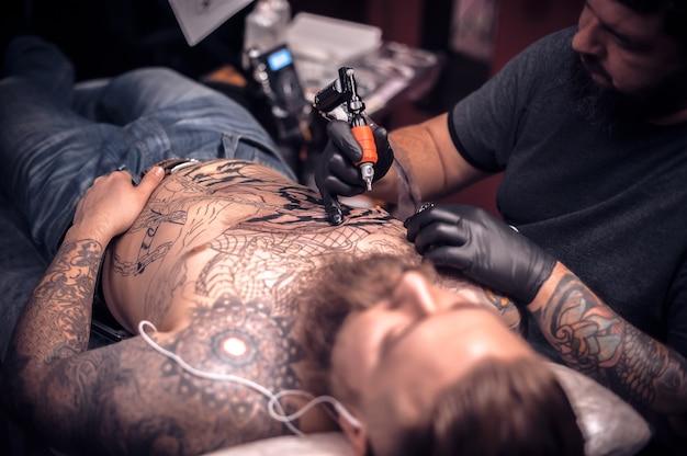 O especialista em tatuagem desenha um estúdio de tatuagem.