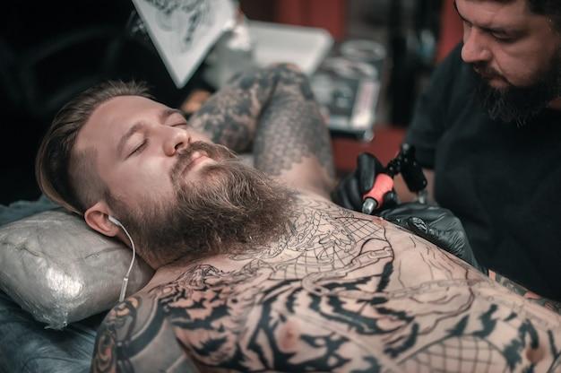 O especialista em tatuagem faz uma tatuagem no estúdio de tatuagem do cliente