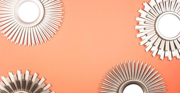 O espelho da parede interior na forma de um sol com sol de bronze do metal irradia o fundo.