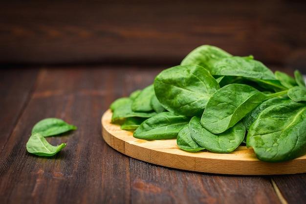 O espinafre suculento fresco sae em uma tabela marrom de madeira. produtos naturais, verduras, alimentos saudáveis