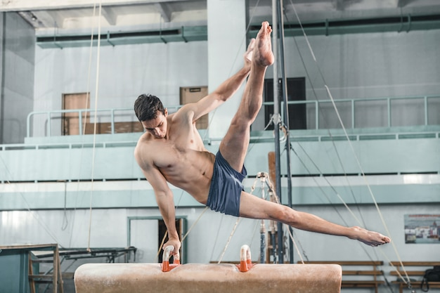 O esportista durante exercício difícil, ginástica esportiva