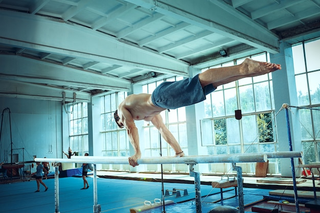 O esportista durante o exercício difícil, ginástica esportiva