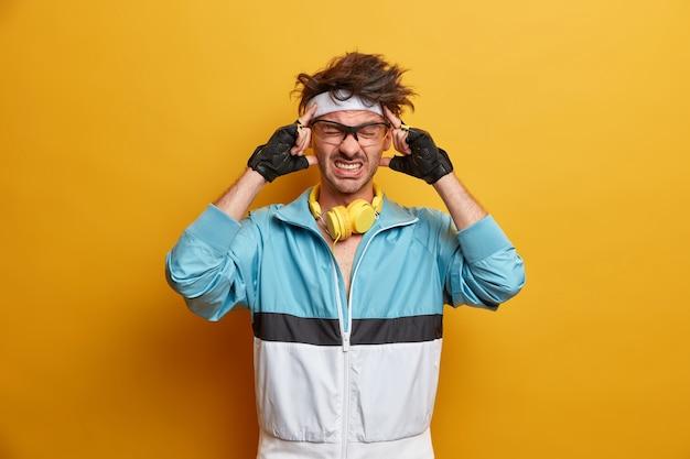 O esportista frustrado sente uma dor de cabeça insuportável após o treino, mantém as mãos nas têmporas, cerra os dentes, concentra-se na tarefa, usa luvas esportivas e roupa ativa, sofre de enxaqueca. cara esportivo doente e cansado