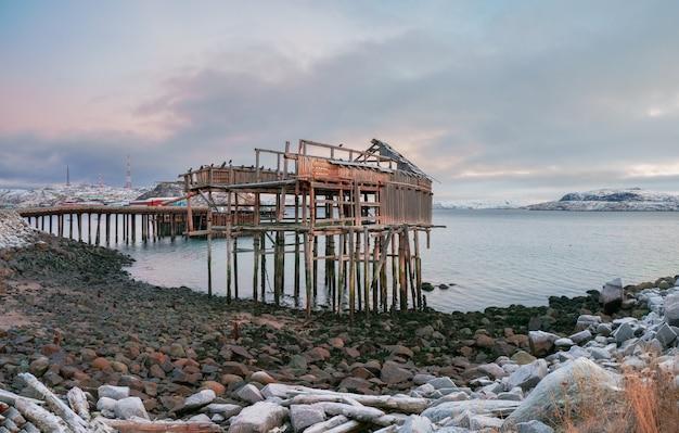 O esqueleto de um galpão de pesca na praia. casa abandonada contra o céu ártico. antiga vila autêntica de teriberka. península de kola. rússia.