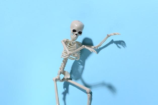 O esqueleto está se esgueirando contra um azul brilhante. conceito de halloween