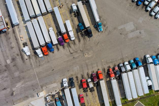 O estacionamento com vista aérea superior para caminhões pesados para na área de descanso na fila de caminhões rodoviários
