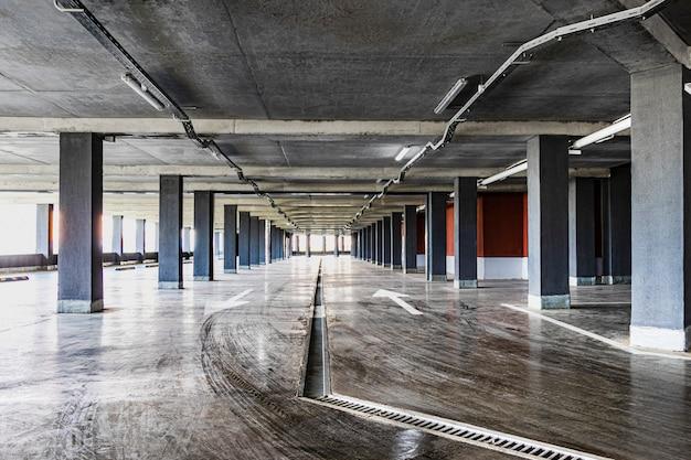 O estacionamento subterrâneo está localizado sob o edifício residencial. um lugar de estacionamento e arrecadação de viaturas pessoais de residentes em edifício de vários pisos.