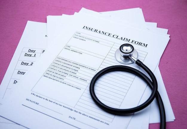 O estetoscópio colocou ao lado do formulário de reivindicação de seguro