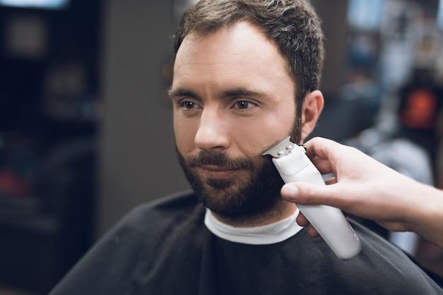 O estilista usa uma máquina de cortar cabelo e um aparador para cortar.