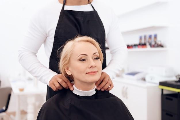 O estilista veste o colar do cabeleireiro no pescoço da mulher madura.