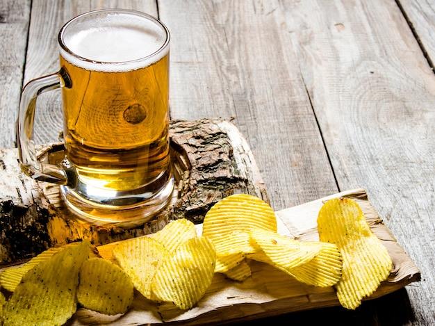 O estilo de cerveja copo de cerveja em um carrinho de bétula e batatas fritas em fundo de madeira