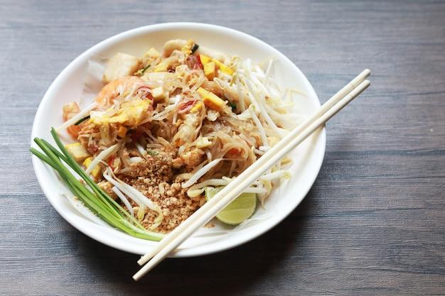 O estilo tailandês fritado do macarronete com camarão tailândia chama a almofada tailandesa, estilo tailandês salteado do macarronete na tabela de madeira.