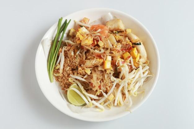 O estilo tailandês fritado isolado do macarronete com camarões e marisco tailândia chama a almofada tailandesa, estilo tailandês salteado do macarronete no branco.