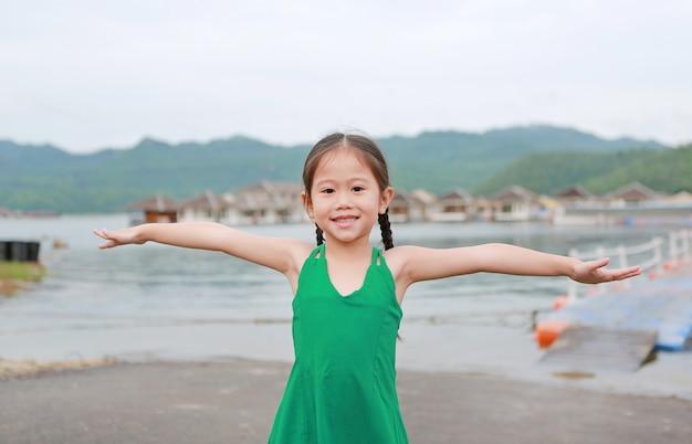 O estiramento asiático pequeno feliz da menina da criança arma-se e relaxa-se no montanhês.