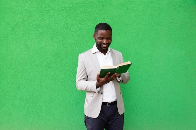O estudante afro-americano com um livro sobre um fundo verde