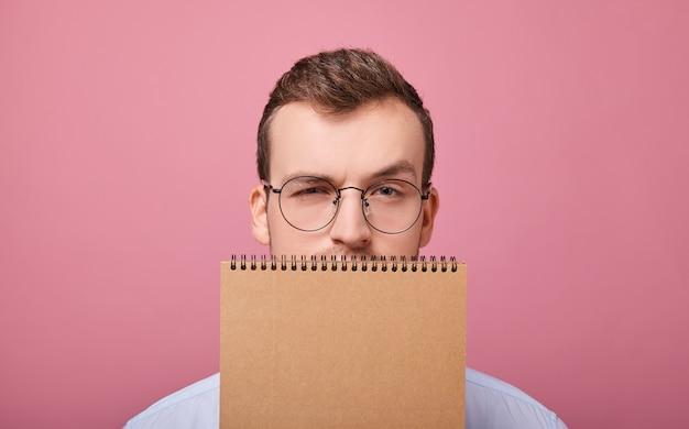 O estudante bonito em copos cobriu o rosto com um caderno marrom de folhas soltas