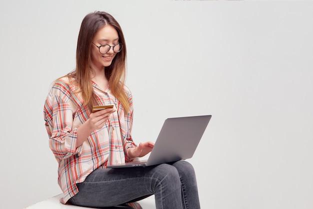 O estudante bonito jovem preenche detalhes do cartão de crédito em um laptop, para pagamento on-line em uma loja on-line.